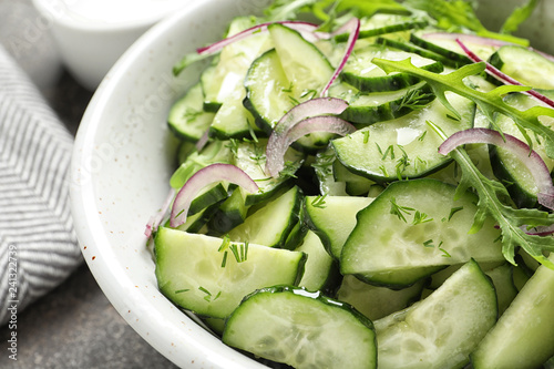 Delicious cucumber salad with onion and arugula in bowl on grey table, closeup