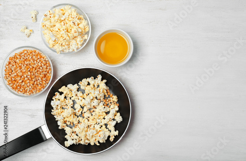Composition with popcorn, oil and space for text on wooden table, flat lay