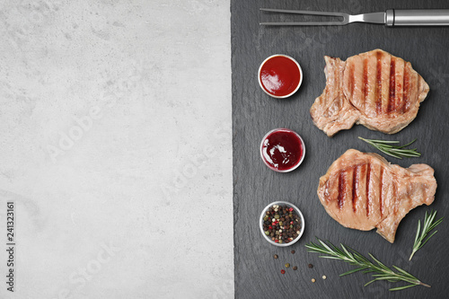 Flat lay composition with grilled meat on slate plate, space for text