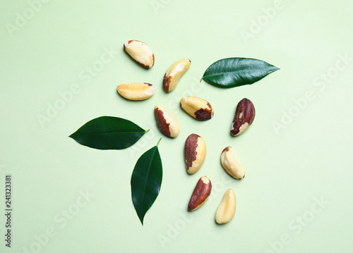 Flat lay composition with Brazil nuts on color background