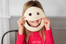 Goofy Little Girl Holding Smiley-shaped Tortilla Against Her Face