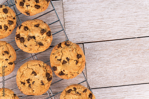 Top view of chocolate chip cookies on a cooling rack, white wooden plank in background. Copy space for your text.