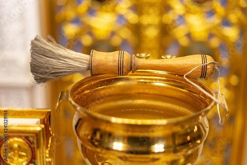 Fotografía  Aspergillum lies on the golden bucket with holy water and Gospel