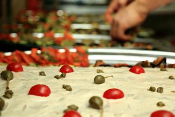 Kucharz przygotowuje talerze z jedzeniem, wędliną, warzywa, owoce w restauracji.