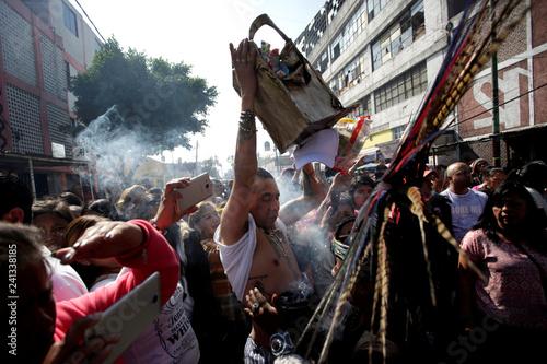 A follower carries offerings to La Santa Muerte (The Saint of Death