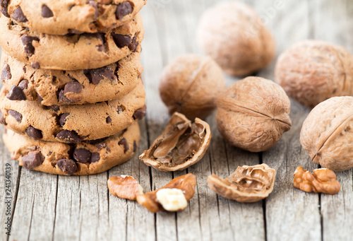 Chocolate chip cookies with walnuts on wooden background