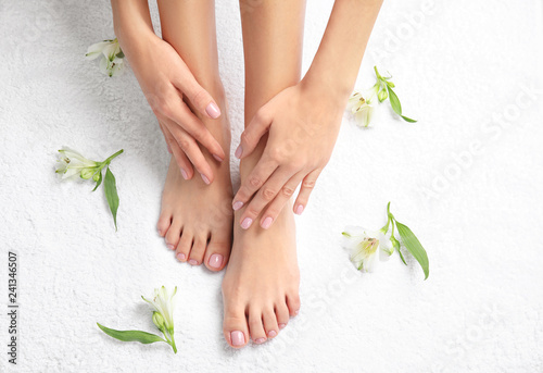 Woman touching her smooth feet on white towel, top view. Spa treatment