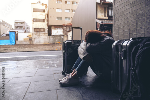 Fotografering  A woman sitting with feeling sad and cry while traveling with a lot of baggages