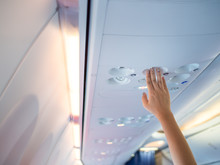 Woman Hand Up To Adjust Console Panel At The Air Conditioner Above The Seat In Airplane