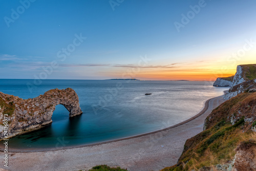Photo The natural arch Durdle Door at the Jurassic Coast in England after sunset