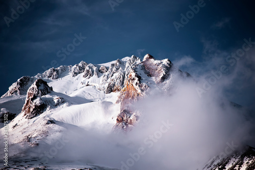 фотография  The rocky summit of Mount Hood is covered with snow and buried in mystical cloud
