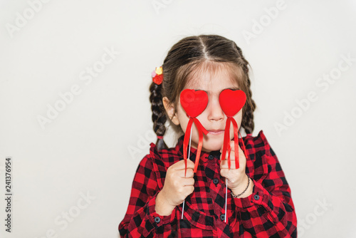 Photo  Little girl playing with red heart shaped balloon.