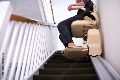 Fotografía  Detail Of Senior Woman Sitting On Stair Lift At Home To Help Mobility
