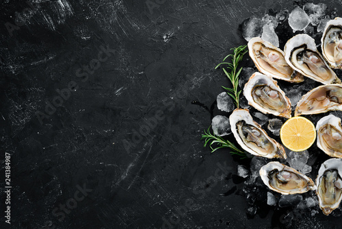 Fototapeta Oysters with ice and lemon on black stone background. Seafood. Top view. Free copy space. obraz