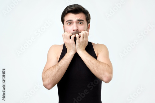 Fotografía  Man covering mouth with hands and round eyes experiencing deep astonishment