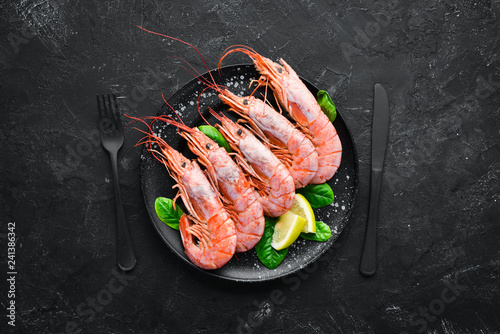 Fototapeta Great Royal Shrimps in a plate. Tiger prawns. Top view. Free space for your text. On the old background.