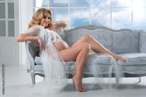 Naked pregnant woman sitting on couch