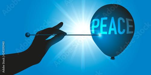 Foto  Concept de la guerre, avec une main qui tient une aiguille pour faire éclater un ballon symbolisant la paix