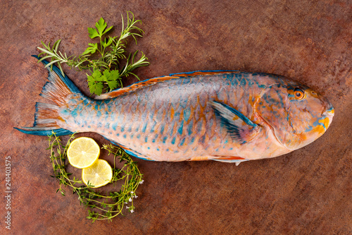 Parrotfish with lemon and herbs on grunge background.