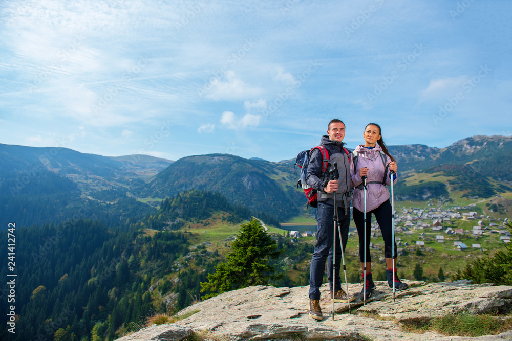 Fototapety, obrazy: Hikers with backpacks relaxing on top of a mountain and enjoying the view of valley
