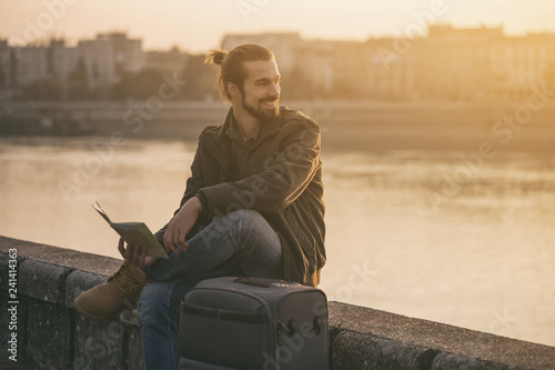 Fototapety, obrazy: Handsome businessman with suitcase holding map of the city and sitting by the river.