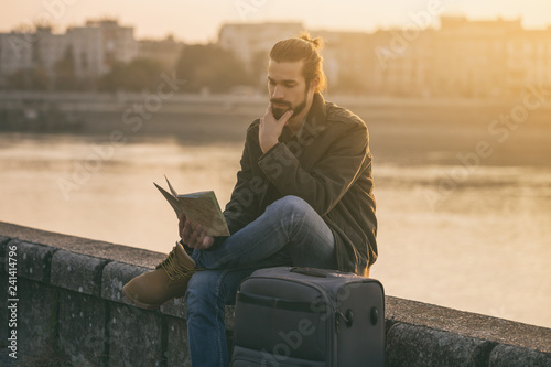 Fototapety, obrazy: Confused businessman with suitcase and city map sitting lost by the river.