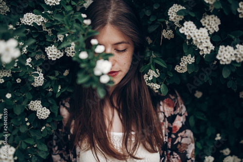 calm portrait of beautiful hipster woman in blooming bush with white flowers of spirea Canvas Print