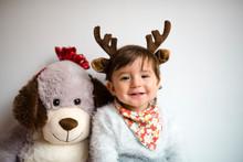 Portrait Of Happy Baby Girl With Reindeer Antlers Headband Beside Her Toy Dog