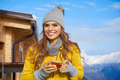 Female in white with cup of tea at the winter weather