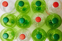 Many Green Plastic Bottles With Caps.