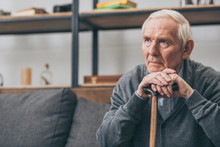 Sad Retired Man With Grey Hair Holding Walking Cane In Living Room