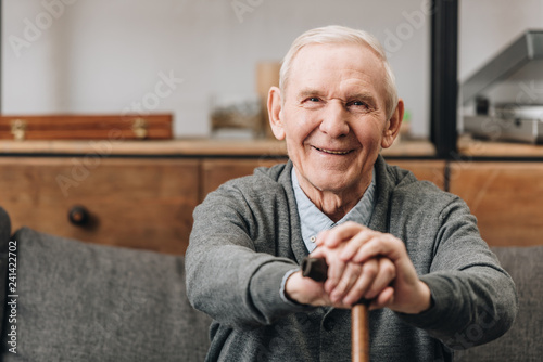 Obraz cheerful pensioner smiling and holding walking cane at home - fototapety do salonu