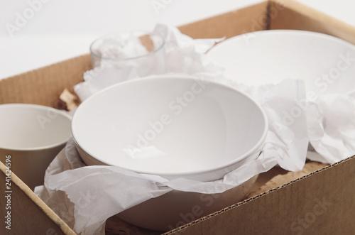 Foto auf Gartenposter Gericht bereit Clean white dishes in paper packed in a cardboard box. Concept relocation