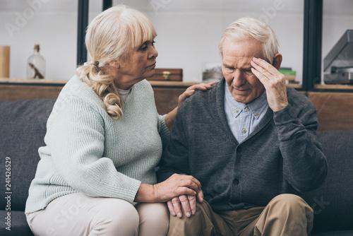 Photo retired woman sitting near senior husband with headache