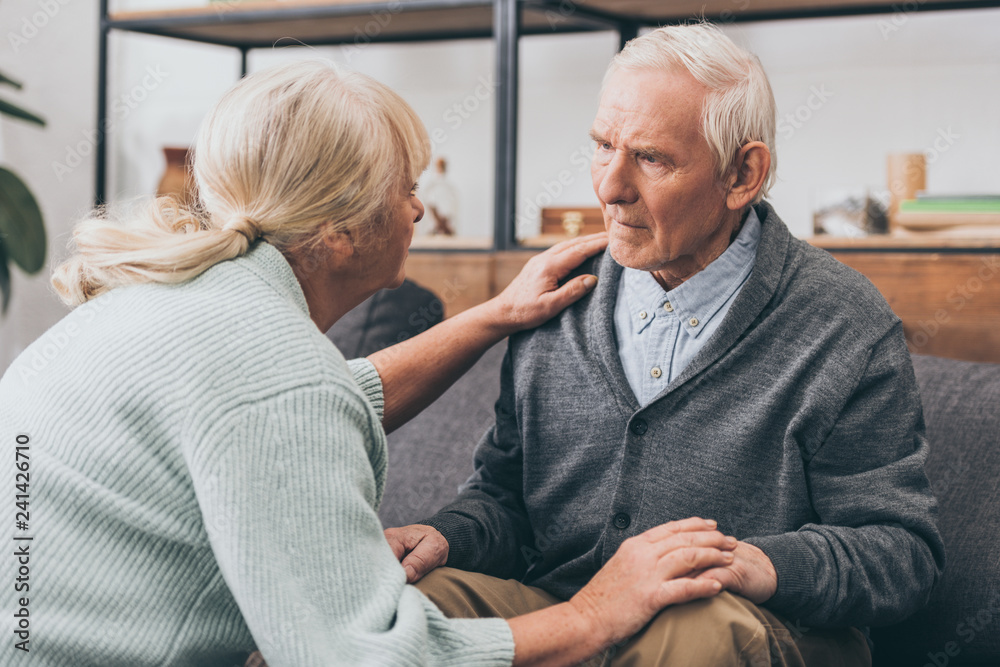 Fototapeta retired couple holding hands and looking at each other at home