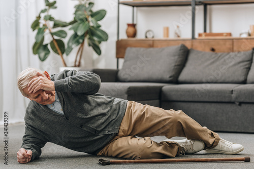Valokuva old men falled down on floor and touching forehead