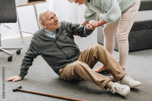 Obraz old woman helping to stand up husband who falled down on floor near walking stick - fototapety do salonu
