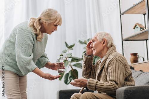 Photo senior woman giving pills and glass of water to old man with walking stick