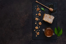 Glass Pot With Fresh Natural Honey, Hoheycomb And Walnuts On A Stone Board. Top View, Close-up, Flat Lay On A Dark Background