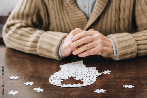 Foto cropped view of senior man playing with puzzles on table
