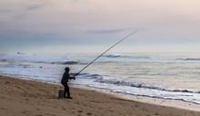 Ocean Sea Fisherman In Silhouette On A Beach Fishing