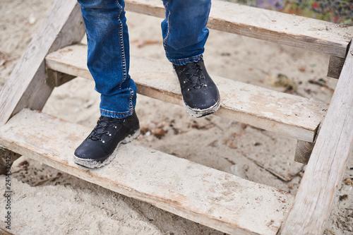 Fototapeta A man Take a walk along the seashore.Men wear shoes and Jeans walk out on a wooden stairs alone obraz na płótnie