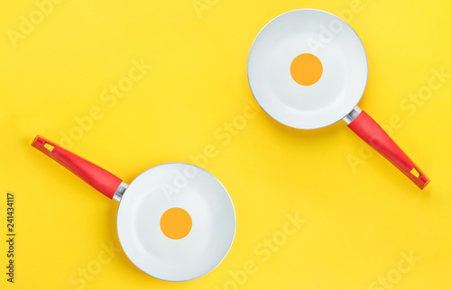 Fotografie, Obraz  Couple of symmetric white ceramic frying pans with red handle on bright yellow background