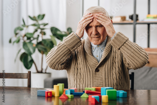 Photo retired man having headache while sitting near wooden toys at home
