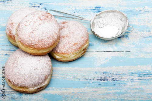 Traditional Polish donuts on wooden background.  Tasty doughnuts with jam.