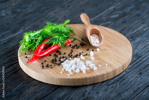 Foto op Canvas Kruiderij rock salt lies on a wooden surface against the background of grains of black pepper, red pepper and dill
