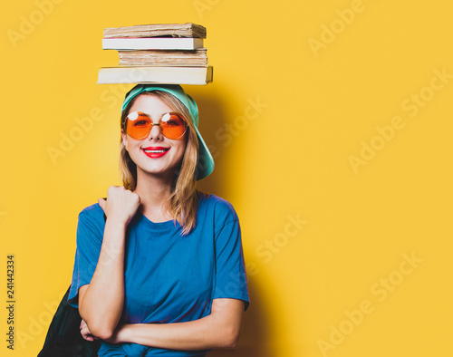 Fotografia  Young style student girl with orange glasses and books on yellow background