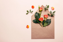 Spring Concept. Paper Envelope With Mini Coral Roses On A Pink Background