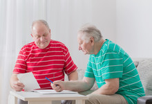 Two Elderly Men With Documents