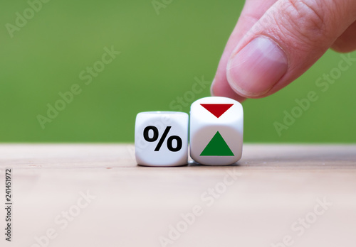 Fotografie, Obraz Hand is turning a dice and changes the direction of an arrow symbolizing that th